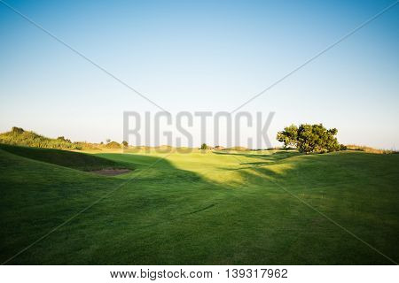 Beautiful golf course with sand trap at sunset