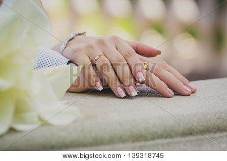 Hands of the newlyweds with gold rings