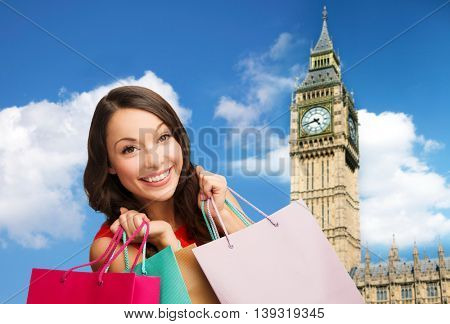 people, holidays, tourism, travel and sale concept - young happy woman with shopping bags over big ben clock tower background