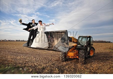 Happy And Funny Wedding Couple In A Scoop Tractor