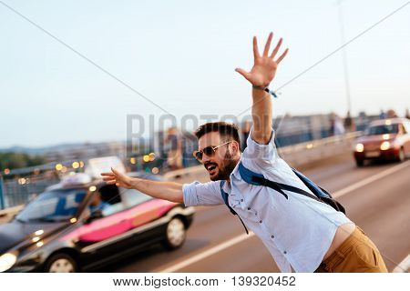 Handsome man trying to catch cab by waving