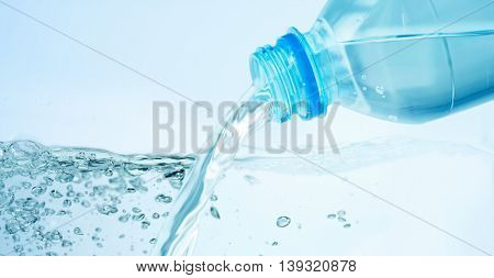 drinking, healthy eating and food storage concept - close up of drinking water pouring from plastic bottle over blue background