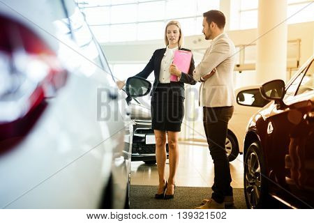 Car salesperson assisting customer at car dealership