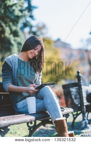 Teenage Girl Drinking Coffe And Using Digital Tablet In Park