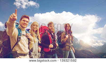 adventure, travel, tourism, hike and people concept - group of smiling friends walking with backpacks over alpine mountains and sky background