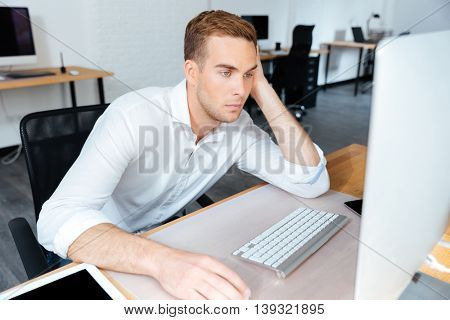Tired bored young businessman sitting and working with computer in office