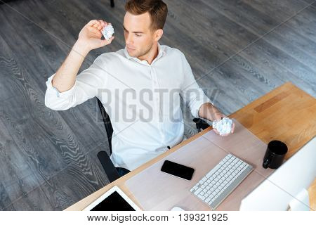 Top view of serious young businessman throwing crumpled paper and working in office