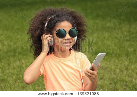 Afro-American little girl in sunglasses listening to music in park