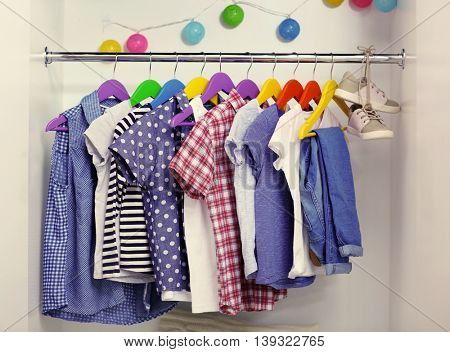 Children clothes hanging on hangers in the wardrobe