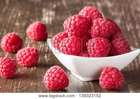 Fresh sweet raspberries in white bowl on the wooden background