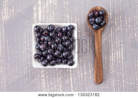 Wooden spoon and white bowl with fresh blueberries on grey wooden background