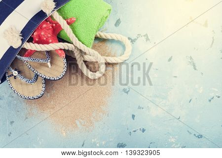 Beach accessories. Bag, towel and flip-flops on stone background. Top view with copy space. Sunny toned
