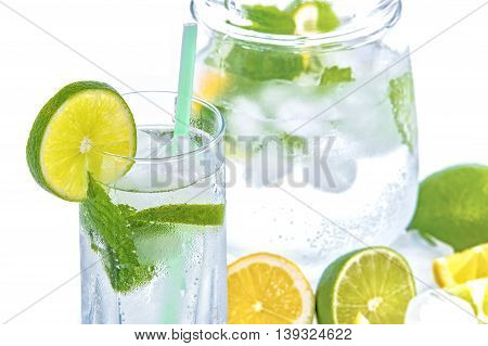 Cold and frosted glass of mineral water with lime mint and ice on a white background
