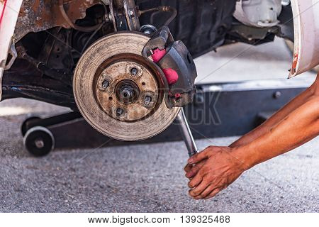 Mechanic technician worked replacing brakes vehicle of automobile at repair service station.