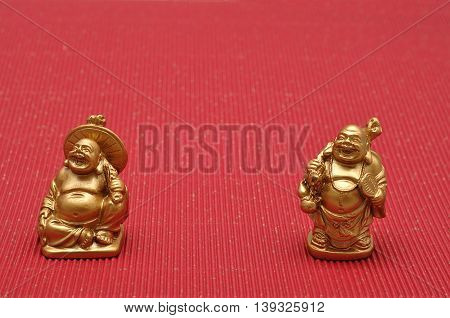 Row of Figurines of laughing and cheerful golden Buddhas