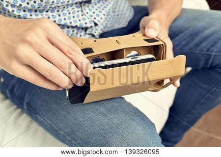 closeup of a young caucasian man mounting his smartphone in a pair of cardboard virtual reality lenses