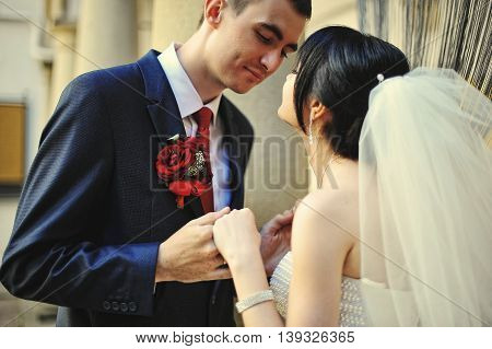 Holding hands newlyweds before kiss at wedding