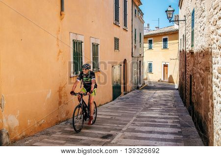 Alcudia Mallorca Spain - May 23 2015: Bicyclist rides along a narrow street of the historical town part of Alcudia with its traditional house and paving stone