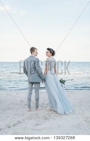 Newly married couple holding hands by the sea.