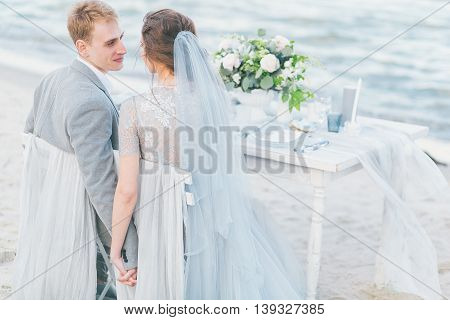 Newly married couple having wedding dinner by the sea.