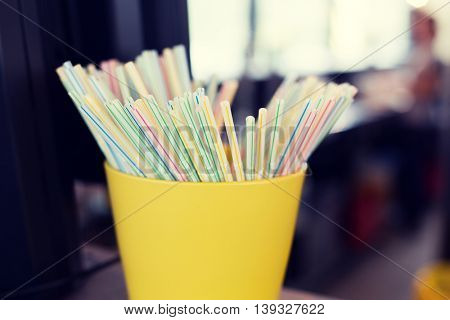 object and device concept - close up of cocktail straws in glass at restaurant