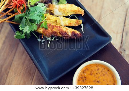asian kitchen, food, culinary and cooking concept - close up of deep-fried snacks on plate at restaurant