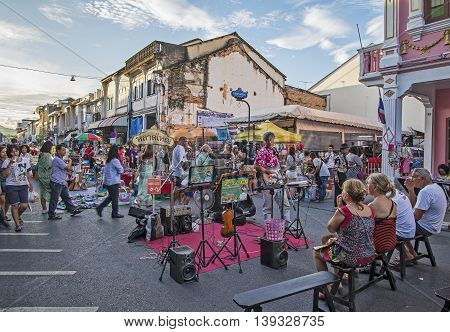 PHUKET THAILAND NOVEMBER 01 2015: Tourists shop at the old town night market (walking street) among old building Chino Portuguese style street of Phuket town in Phuket Thailand.