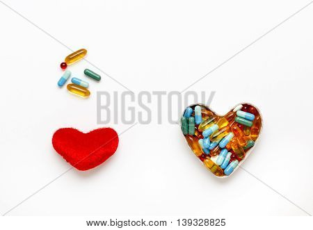 red plush heart and pills in shape of heart top view isolated