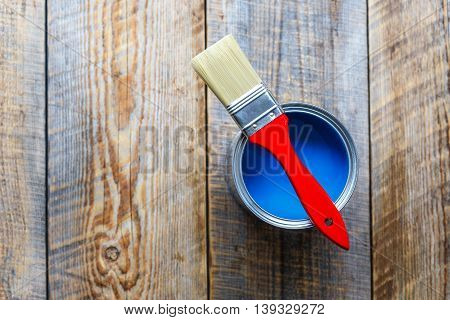 painting with open can of blue paint and red brush on wooden background top view