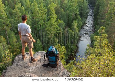 Backpacker staying on big rock above the green forest and river