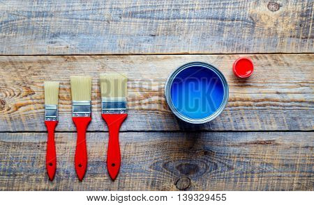 process of preparation for painting wooden floor at home with blue and red paint top view