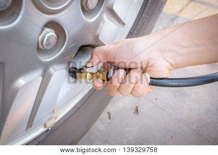 Filling air pump into a car tire before driving car