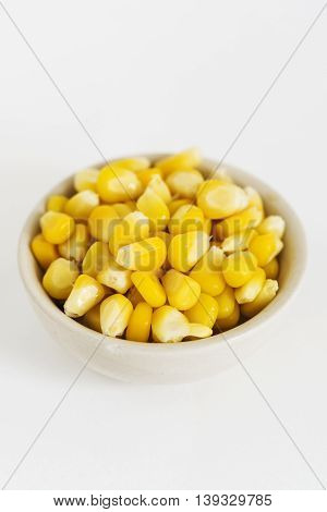 Grains of Corn in a dish on White Background.