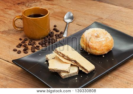 coffee and wafer stick and donuts sugar on black plate with wood background