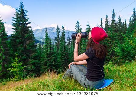 Woman resting on green meadow and drinking water. Concept of active leisure tourism. Young woman enjoying the summer and mountains landscape. Girl drinks water from a bottle