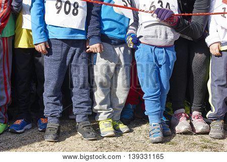 Children athletics runner on a cross country race. Start. Horizontal