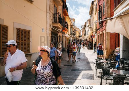 Alcudia Mallorca Spain - May 23, 2015: Couple of tourist walking along a narrow street of the historical town part of Alcudia and eat ice-cream