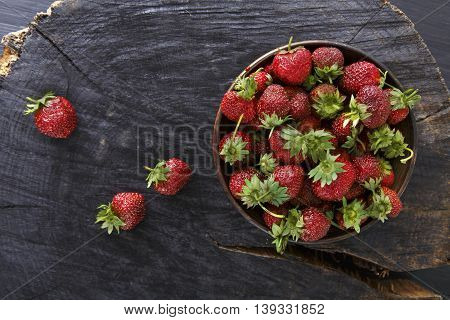 Red fresh strawberries on black rustic wood background. Bowl with natural ripe organic berries with peduncles on wooden circle cut out, top view with copy space