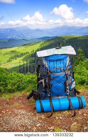 Camping gear and backpack on a background of mountains. Backpack traveler and map on mountains background. Mountains landscape and big backpack with map
