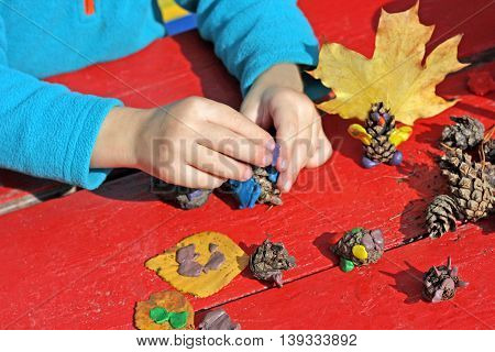 Child to play outdoors. The image is part of small child playing with plasticine in the street behind a red wood Desk. A child plays with clay and various natural materials with different shapes.