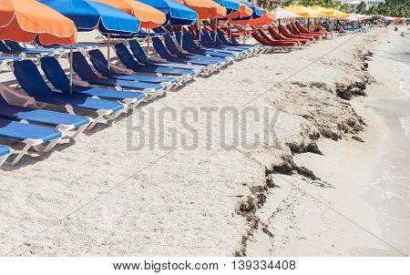Beach scene - Blue reclining chairs with colorful orange, blue and yellow beach umbrellas on sandy beach near tidal rising points.