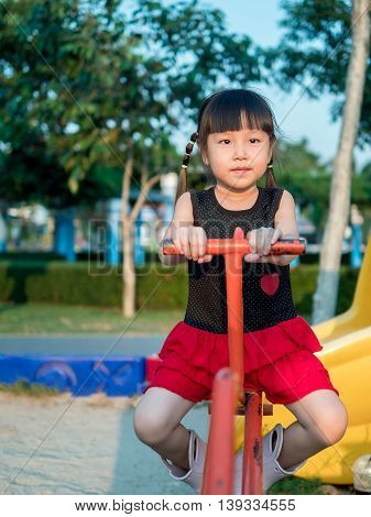 Happy kid asian baby child playing on a seesaw