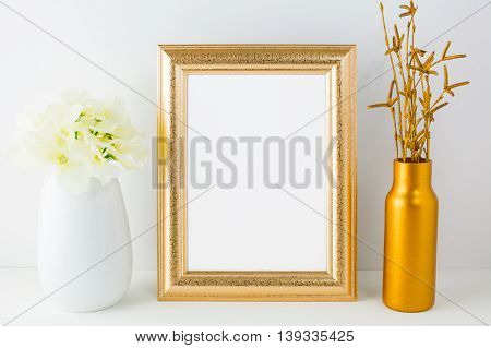 Frame mockup with golden vase and ivory hydrangea. Empty white frame mockup for design presentation. Portrait or poster frame mockup.