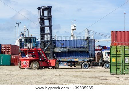 Labuan,Malaysia-July 21,2016: Forklift handling container box loading at the docks with truck at Labuan island port.The port has been managed by Labuan Liberty Port Management Sdn Bhd since 1988.