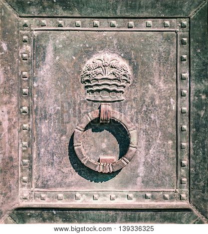 Detail of the circular door knocker of a iron gate of a castle.