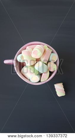 assorted marshmallow candies on a grey wooden background