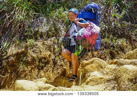 Ranau,Sabah-March 12,2016:Mountain porter transporting heavy luggage through Timpohon trail to Laban Rata at 3,273 meter above sea level, the last stop before reaching Kinabalu peak.