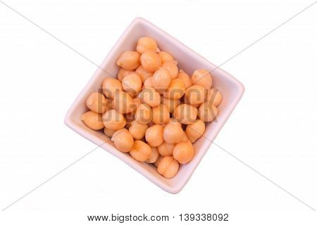 Boiled chickpeas on a square bowl on a white background seen from above