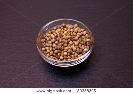 Coriander seeds of bowl on a slate floor