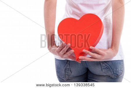 Girl holding heart behind back, isolated on white